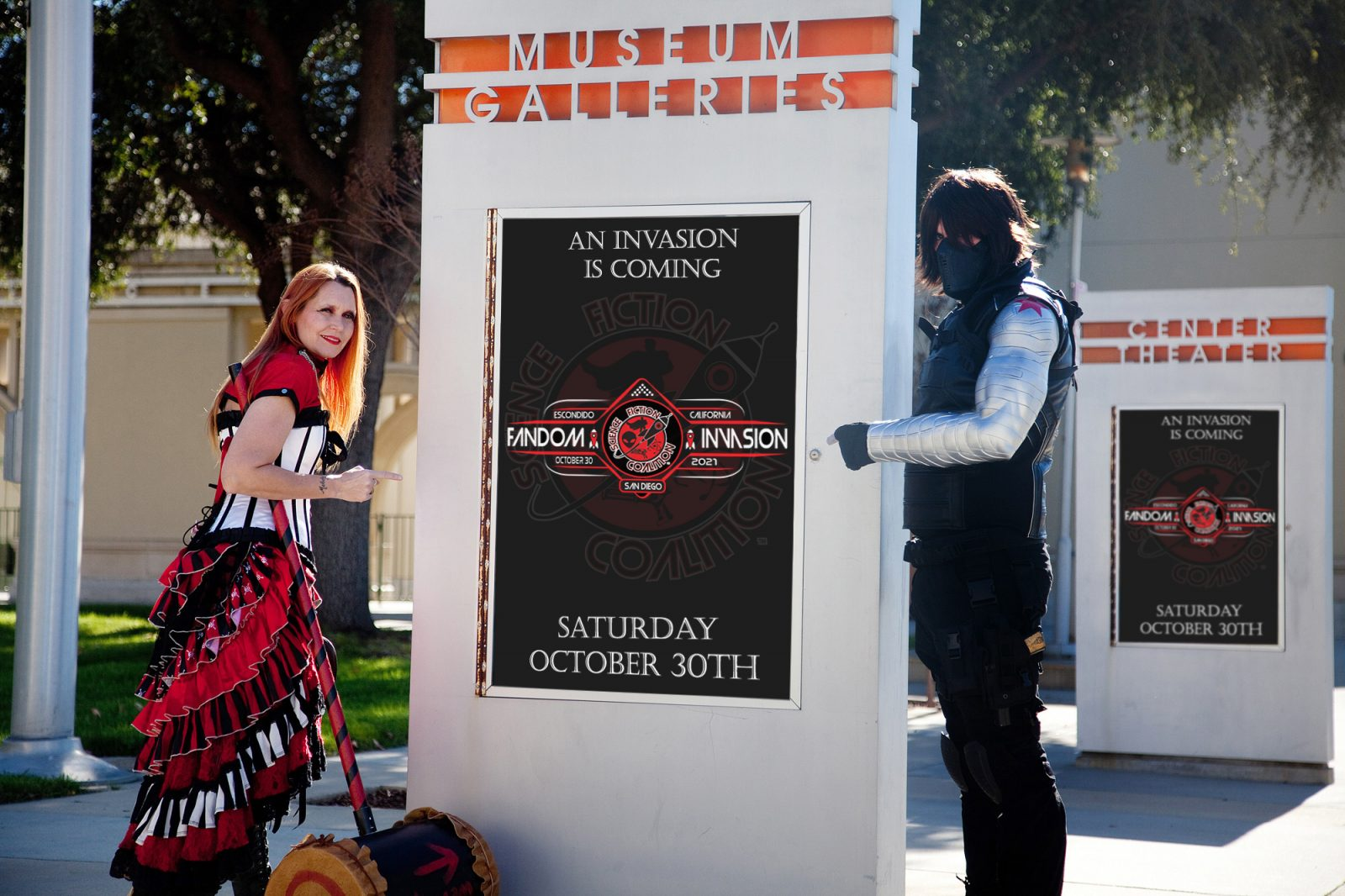 Harley Quinn and Winter Soldier cosplayers point at a Fandom Invasion poster stating that an Invasion is coming.